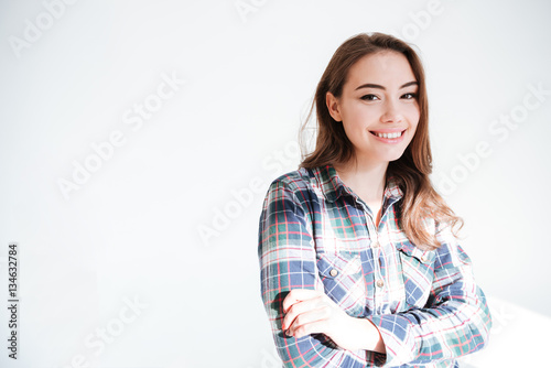 Poster Cheerful pretty young woman standing with arms crossed