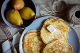 Pancakes on a large gray plate, dairy products and pickled pears. Country style