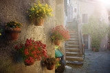 Spring streets of the old Tuscan town. Colorful flowers bloom an