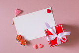 Valentine day composition: red gift box with bow, stationery / photo template with clamp, small hearts, candy and spring flowers on light pink background. Top view.