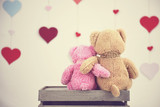 Two toy teddy bears sitting in front of hearts - 134694188