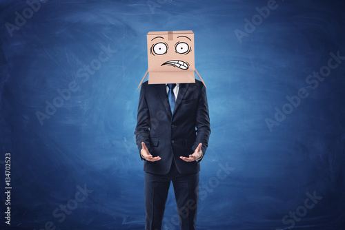 Businessman is wearing cardboard box with drawn shocked face on his head Poster