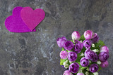 A two decorative pink and purple  hearts and a flowers on gray