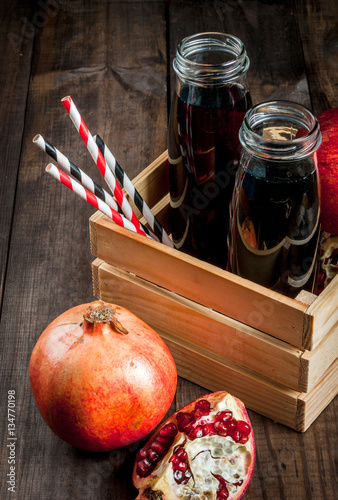 Homemade pomegranate juice in bottles in wooden box, with straws and fresh whole and sliced pomegranates. copy space, close view