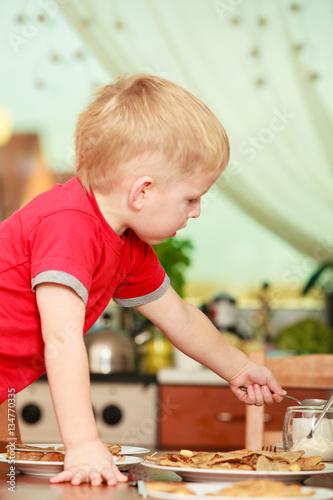 Little boy preparing pancakes for breaktfast