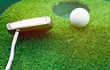 Golf ball and putter near to hole