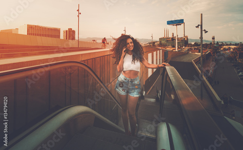 Young curly hipster brunette girl speaking on her cell telephone while standing on the moving staircase, pretty woman talking on smart phone with friend on escalator in urban setting during sunset