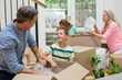Parents and kids unpacking carton boxes in living room