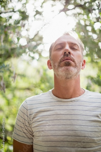 Man meditating against bright sunlight
