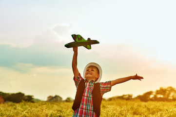 a boy plays with a plane . Dreams of becoming a pilot