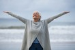 Senior woman with arms outstretched standing on the beach