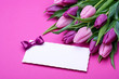 Violet tulips and greeting card on pink