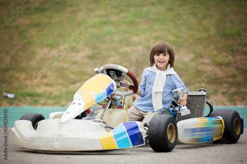Poster Cute child, riding go cart, wins champion cup, happiness winner concept