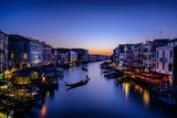 Long exposure of the Grand Canal seen from Rialto bridge at sunset. Gondolas seem resting on the water. The atmosphere is magical and surreal as Venice
