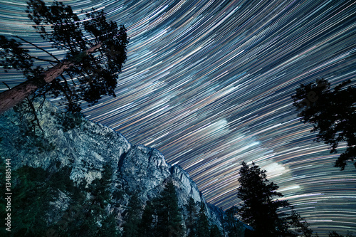 Fototapeta Long star trails of the milky way pass over the top of Kern canyon in a long exposure showing the granite cliffs and pine trees