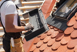 Installation of mansard windows on a new roof of red tiles