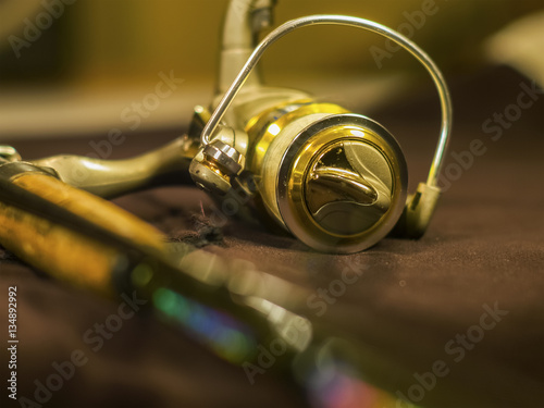 Golden fishing reels on the rod Poster