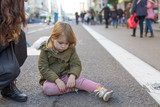 three years old blonde lovely caucasian girl child, with crying and sad expression and tear in face, next to mother, sitting on grey asphalt at pedestrian Gran Via Street in Madrid city, Spain