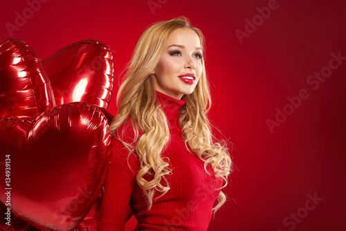 Poster Beautiful blond woman posing on red . Valentine concept