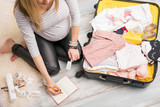 Pregnant woman packing for hospital and taking notes - 134959529
