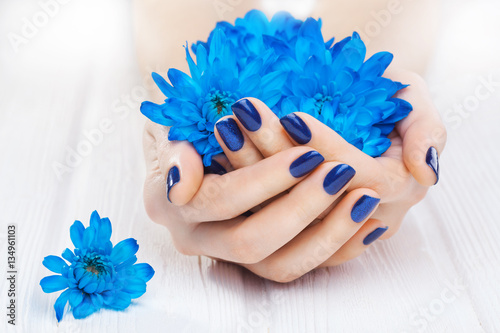 Staande foto Manicure blue manicure with chrysanthemum flowers. spa