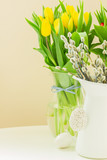 fresh yellow tulips and willow catkins in pot with easter eggs