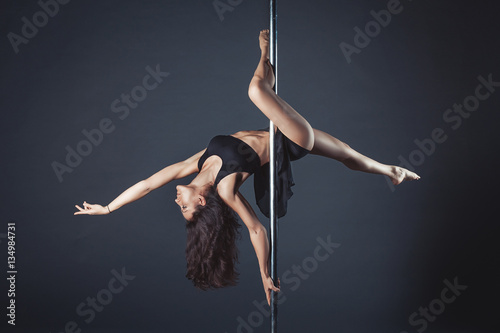 Plakat Young slim pole dance girl of asian appearаnce on a black studio background