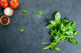 Fototapety Cooking background. Kitchen table with spices (salt and pepper), mozzarella, tomatoes and fresh basil, top view, copy space