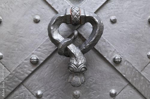 Poster Antique metal door knocker in the shape of a serpent affixed to an antique metal door