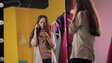 Young beautiful female is talking on cell phone standing in front of mirror. Discussing work questions and checking information in another mobile device held in hands woman is concentrated on solving