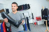 Man in shop holding riding boot - 135003949