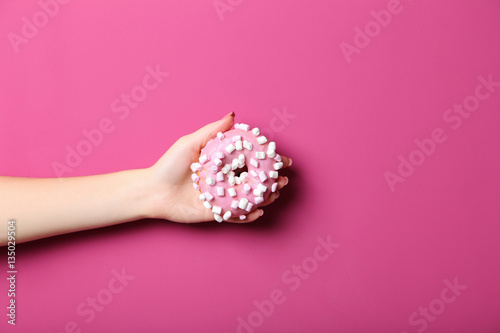 Female hand holding sweet donut on pink background - 135029504