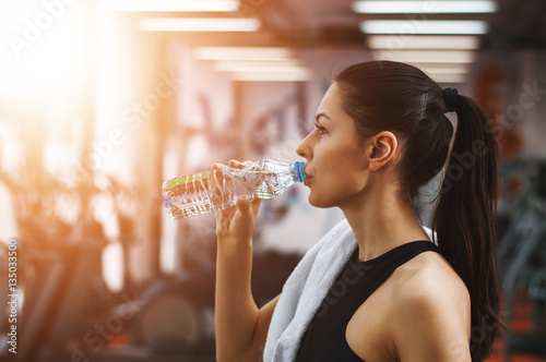Poster Refreshing after workout. Beautiful young woman in sports clothi