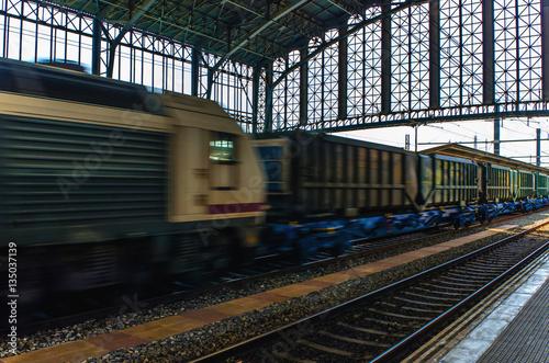 Poster freight train speeding through train station