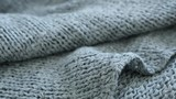 Tilting on sweater knitting style and details 4K 2160p 30fps UltraHD footage - Fine texture and knitwork of female green cloth shallow DOF 3840X2160 UHD tilt video
