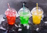 colorful cold drinks in plastic cups with ice