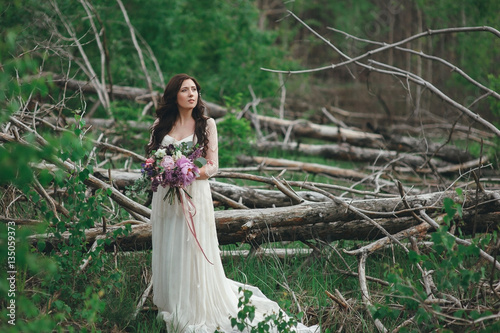 Poster Beautiful bride in the forest with a large bouquet of different flowers