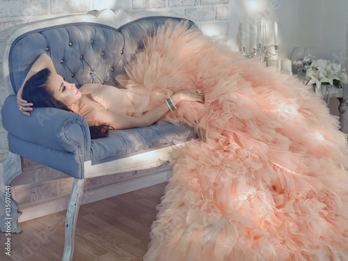 Poster Beautiful lady in gorgeous couture dress on sofa