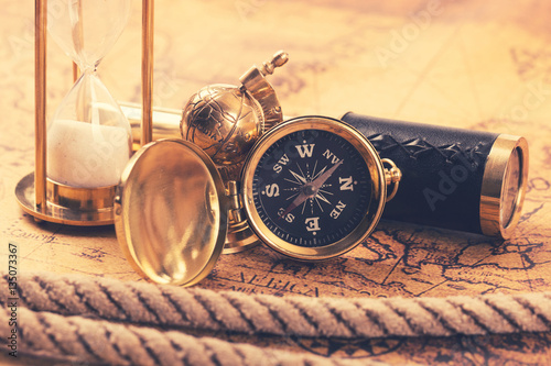 Fototapeta vintage compass and nautical items on ancient world map