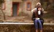 Glückliche junge modisch gekleidete Frau im Winter sitzt auf einer Mauer
