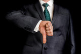 Businessman showing gesture with thumb down - 135077334