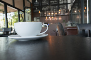 Cup of coffee on wooden table in cafe.