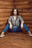 Portrait of young sexy dark-haired model wearing skinny high-waisted jeans, striped tied up shirt with pockets, choker and golden sneakers sitting with her legs spread on the wooden floor in log cabin