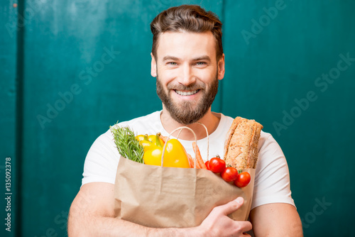 Handsome man holding a paper bag full of healthy food on the green background