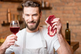 Portrait of a handsome man in apron holding raw meat with wine on the kitchen