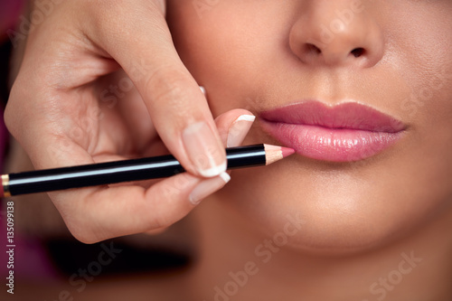 Professional makeup artist applying lipstick Poster