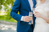 bride and groom in the park with champagne;
