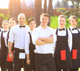 large group of waiters and waitresses who stand in the row behind each other