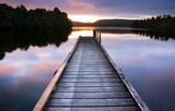 New Zealand, South Island - Wooden jetty on still lake reflectin