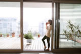 Fototapety Woman relaxing on balcony holding cup of coffee or tea